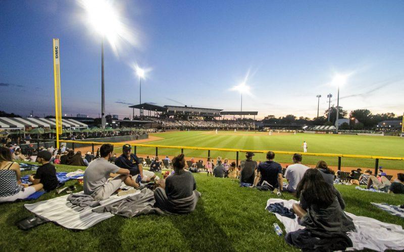 A crowd of people sitting near Jimmy John's baseball field