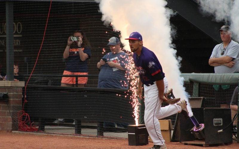 An utica unicorns baseball player running with smoke in the background